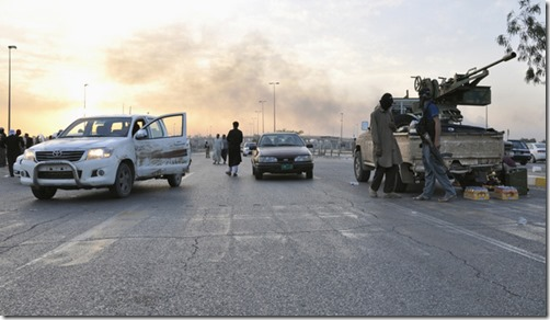 Fighters of the Islamic State of Iraq and the Levant (ISIL) stand guard at a checkpoint in the northern Iraq city of Mosul, June 11, 2014. Since Tuesday, black clad ISIL fighters have seized Iraq's second biggest city Mosul and Tikrit, home town of former dictator Saddam Hussein, as well as other towns and cities north of Baghdad. They continued their lightning advance on Thursday, moving into towns just an hour's drive from the capital. Picture taken June 11, 2014. REUTERS/Stringer (IRAQ - Tags: CIVIL UNREST POLITICS CONFLICT) - RTR3TDQT